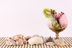 Ice cream with Kiwi. Ice cream with chocolate decoration and sea shells and seashells on white background stock photos