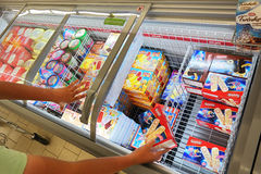 Ice cream in a Lidl supermarket. BELGIUM - JULY 2015: Shopper and the freezer with ice cream products in a Lidl supermarket. Lidl is a German discount chain Royalty Free Stock Images