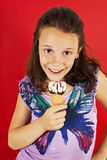 Ice cream little girl excited. And happy eating ice cream cone. Isolated on a red background Royalty Free Stock Image