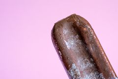 Ice cream lolly in chocolate glaze close-up with condensate and icing frost on a soft pink background.  stock images