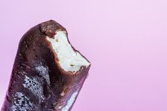 Ice cream lolly in chocolate glaze close-up with condensate and icing frost on a soft pink background.  stock image