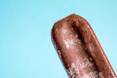Ice cream lolly in chocolate glaze close-up with condensate and icing frost on a summer blue sky background.  stock photos