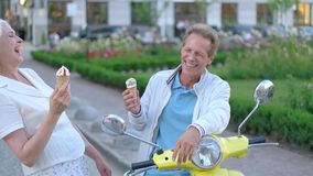 Ice cream on man's nose. Mature couple is laughing. Magic of summer. Look at yourself, sweetie stock video footage