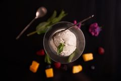 Ice cream with mascarpone cheese in a glass ice-cream bowl decorated with mint leaves on a dark background with slices of mango, b royalty free stock images