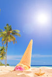 An ice cream melting in the sand on a tropical beach Royalty Free Stock Images