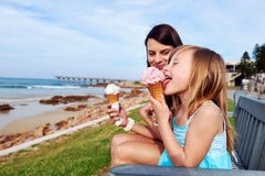 Ice cream mom daughter. Mom and daughter enjoy fun ice cream at the beach smiling laughing joy on summer vacation royalty free stock photography