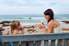 Ice cream mom daughter. Mom and daughter enjoy fun ice cream at the beach smiling laughing joy on summer vacation stock images