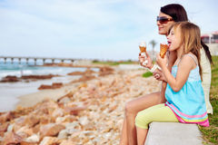 Ice cream mom daughter. Mom and daughter enjoy fun ice cream at the beach smiling laughing joy on summer vacation royalty free stock images