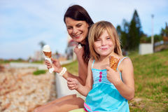 Ice cream mom daughter. Mom and daughter enjoy fun ice cream at the beach smiling laughing joy on summer vacation royalty free stock photos