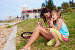 Ice cream mom daughter. Mom and daughter enjoy fun ice cream at the beach smiling laughing joy on summer vacation stock photography
