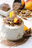 Ice cream with peach, chocolate and nuts. Ice cream with peach, chocolate and nuts on white plate Royalty Free Stock Photography