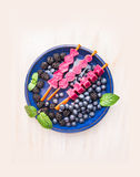 Ice cream pops with  blackberries and blueberries in blue plate on white wooden background, top view. Ice cream pops with  blackberries and blueberries in blue Stock Images