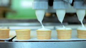 Ice cream pouring in waffle cones. Automated production line at food factory. Ice cream machine. Ice cream production line. Ice cream manufacturing process stock footage
