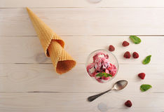 Ice cream with raspberries and a waffle cone. On white wooden background - top view royalty free stock photos