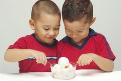Ice Cream Ready to Eat - #4. Two preschool brothers digging into a large bowl of strawberry-cheesecake ice cream stock photos