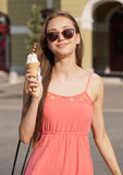 Ice cream refreshment. Beautiful young brunette woman having ice cream refreshment in summer sunshine Royalty Free Stock Images