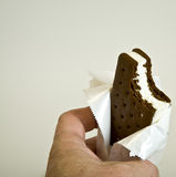 Ice cream sandwich. An ice cream sandwich in hand missing a bite Royalty Free Stock Photos