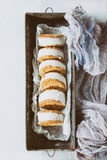 Ice cream sandwiches in cookies. Set of homemade ice cream sandwiches in oat cookies with almond sugar crumbs on baking paper in old metal bowl over gray texture royalty free stock photos