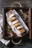 Ice cream sandwiches in cookies. Set of homemade ice cream sandwiches in oat cookies with almond sugar crumbs on baking paper in woden tray over dark metal stock images