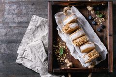 Ice cream sandwiches in cookies. Set of homemade ice cream sandwiches in oat cookies with almond sugar crumbs on baking paper in woden tray over dark metal royalty free stock photos