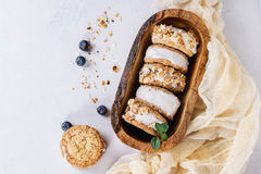 Ice cream sandwiches in cookies. Set of homemade ice cream sandwiches in oat cookies with almond sugar crumbs, blueberries and mint on in olive wooden bowl over royalty free stock image
