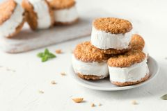 Ice cream sandwiches. With nuts and wholegrain cookies. Homemade vanilla  on white background royalty free stock image