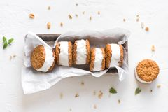 Ice cream sandwiches. With nuts and wholegrain cookies. Homemade vanilla  on white background stock photos