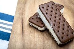 Ice cream sandwiches. Image with a rustic feeling of two Ice Cream sandwiches on a wooden table stock photos