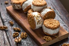 Ice cream sandwiches. With nuts and wholegrain cookies. Homemade vanilla  on dark wooden background stock images