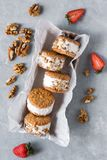 Ice cream sandwiches. With nuts and wholegrain cookies. Homemade vanilla  on gray concrete background stock images