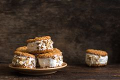 Ice cream sandwiches. With nuts and wholegrain cookies. Homemade vanilla and walnuts   on dark wooden table, copy space royalty free stock image