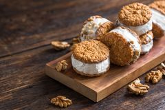 Ice cream sandwiches. With nuts and wholegrain cookies. Homemade vanilla and walnuts   on dark wooden table, copy space royalty free stock photos