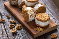 Ice cream sandwiches. With nuts and wholegrain cookies. Homemade vanilla and walnuts   on dark wooden table, copy space stock photo