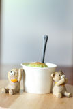 Ice cream scoop with miniature bear doll on wooden plate Royalty Free Stock Photo