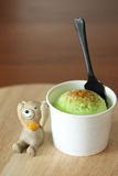 Ice cream scoop with miniature bear doll on wooden plate Royalty Free Stock Image