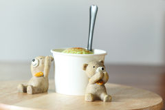Ice cream scoop with miniature bear on wooden plate Royalty Free Stock Photos