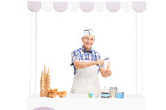 Ice cream seller making an ice cream behind a stall Royalty Free Stock Image