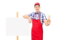 Ice cream seller standing by a blank signboard Stock Image
