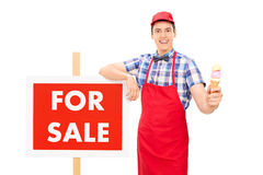 Ice cream seller standing by a for sale sign Stock Images