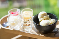 Ice cream served with various topping in small glass on wooden t Stock Images