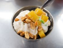 Ice cream sprinkled with peanuts and coconut milk it.  stock photography