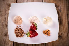 Ice cream with strawberries, chocolate and almonds. Ice cream balls with strawberries, almonds and chocolate on a plate Stock Images