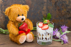 Ice cream with strawberries, mint and muesli against the backdrop of a teddy bear. Wooden rustic table. Close-up Royalty Free Stock Photography