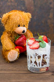 Ice cream with strawberries, mint and muesli against the backdrop of a teddy bear. Wooden rustic table. Close-up Stock Photography