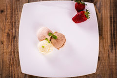 Ice cream with strawberries on a plate. Ice cream balls with strawberries and mint on a plate Stock Image