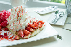Ice cream strawberry crepe dessert on white dish wood table in c Stock Photos