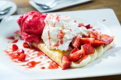 Ice cream strawberry crepe dessert on white dish wood table in c Royalty Free Stock Photo