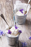 Ice cream with sugared violets. Ice cream, served in little metal pail with sugared violets on old wooden table stock photography