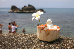 Ice cream on summer coconut with orchid flower. On the tropical beach with people blurred behind Stock Image