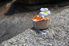 Ice cream on summer coconut with orchid flower. On the tropical beach with people blurred behind Royalty Free Stock Image